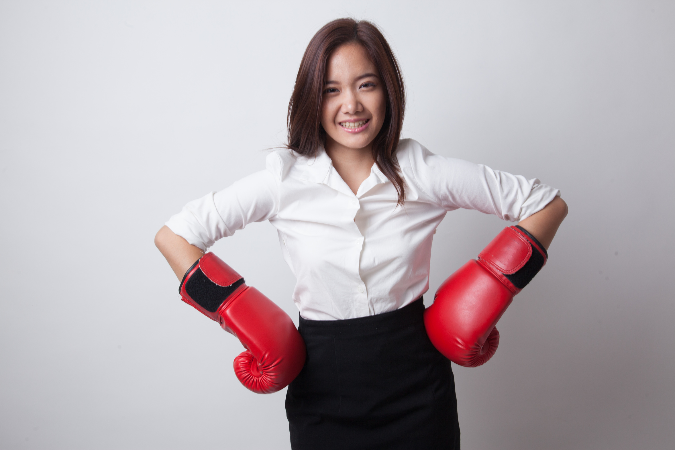 Young Asian woman with red boxing gloves on white background
